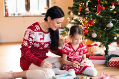 Young mother with daugter at Christmas tree at home. Stock Images