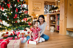 Young mother with daugter at Christmas tree at home. Stock Photography