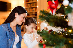 Young mother with daugter decorating Christmas tree together. Royalty Free Stock Image