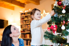 Young mother with daugter decorating Christmas tree together. Stock Photo