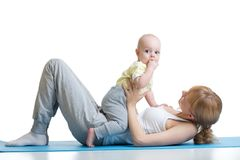 Young mother does fitness exercises together with baby boy isolated on white background. Young mother does fitness exercises together with baby boy isolated on Stock Photography