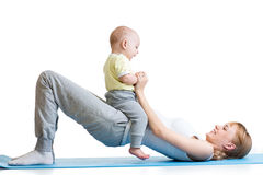 Young mother does fitness exercises together with Royalty Free Stock Image