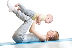 Young mother does fitness exercises together with kid boy isolated. Young mother does fitness exercises together with baby boy isolated Royalty Free Stock Image