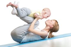 Young mother does fitness exercises together with kid boy isolated. Young mother does fitness exercises together with baby boy isolated Stock Photo
