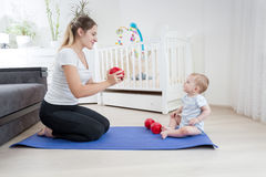 Young mother doing fitness and giving dumbbells to her baby. Con Stock Images