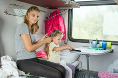 Young mother doing her hair daughter on a cot in a train Royalty Free Stock Image
