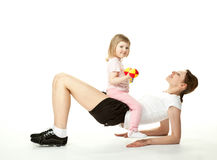 Young mother doing sport exercises with daughter Stock Photos