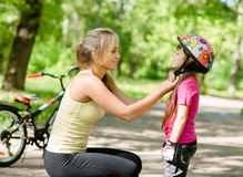 Young mother dresses her daughter's bicycle helmet Royalty Free Stock Images