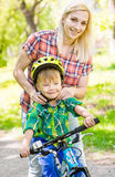Young mother dresses her son bicycle helmet stock photo
