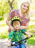 Young mother dresses her son bicycle helmet royalty free stock photo