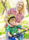 Young mother dresses her son bicycle helmet Royalty Free Stock Image