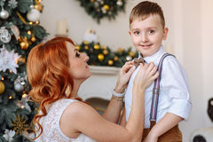 Young mother dresses his son a bow tie on the background of Christmas decorations Royalty Free Stock Photo