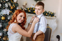 Young mother dresses his son a bow tie on the background of Christmas decorations Stock Images