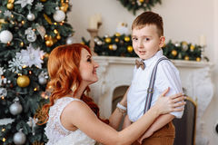 Young mother dresses his son a bow tie on the background of Christmas decorations Stock Photos