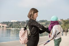 Young mother dressing her son in a pullover. As they enjoy a day walking on a waterfront promenade in the sunshine stock photography