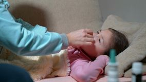 Young mother dripping sick daughter drops in the nose. stock footage