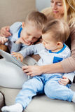 Young mother embosoming two sons playing digital tablet Royalty Free Stock Images