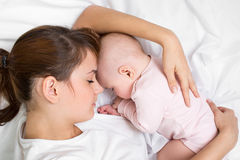 Young mother embracing her sleeping baby Stock Photography