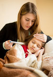 Young mother embracing sick daughter and checking thermometer Royalty Free Stock Image