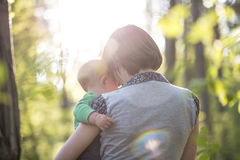 Young mother enjoying a beautiful moment of love, tenderness and. Care with her baby boy while walking through a sunlit park or forest in a conceptual image Stock Photo