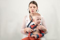 A young mother examines a boy with a stethoscope. Female doctor with stethoscope in hospital. Professional medicine health clinic. Practitioner. Medical Royalty Free Stock Images
