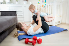 Young mother exercising on floor with her baby boy Stock Photo
