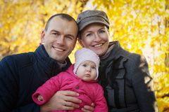 Young mother and father and baby girl have fun in autumn Stock Image