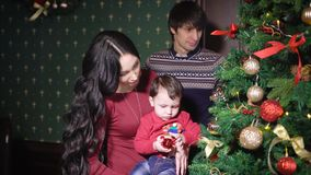 Young mother and father taught his young son to decorate a Christmas tree in their cozy home. Toddler holding a stock video