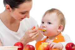 Young mother feeding baby daughter royalty free stock photos