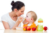 Young mother feeding baby girl royalty free stock image