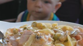 Young mother is feeding the baby on her lap pasta in Italy. Kid 1 year, it is in a green t-shirt stock video footage