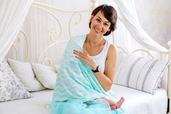 Young mother feeding baby to your breast. Young mother feeds the child at the breast on the bed Royalty Free Stock Images
