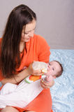 Young mother feeding bottle six-month baby girl Royalty Free Stock Image