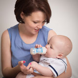 Young Mother Feeding Her Baby Boy With A Milk Bottle Stock Images
