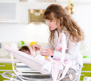 Young mother feeding her baby with a spoon Stock Image