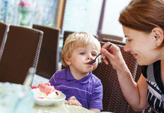 Young mother feeding her little boy son with ice-cream Stock Image