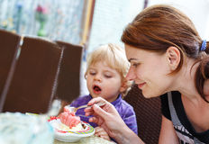 Young mother feeding her little boy son with ice-cream Royalty Free Stock Photo