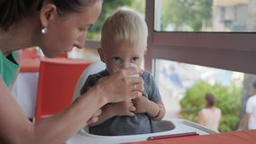 A young mother is feeding her little cute son at a table during breakfast in the morning in a cafe. stock video footage