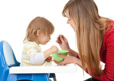 Young mother feeding hungry baby in highchair Royalty Free Stock Photography