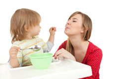 Young mother feeding hungry baby in highchair Stock Images