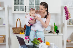Young mother feeds child in the kitchen. Young mother feeds little daughter  in the home kitchen. Happy family Royalty Free Stock Image