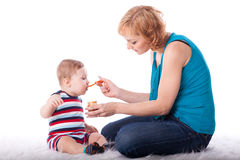 Young mother feeds  her baby. Stock Photos