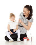 Young mother feeds  her baby. Young mother feeds  her baby on a white background. Happy family Royalty Free Stock Image