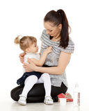 Young mother feeds  her baby. Young mother feeds  her baby on a white background. Happy family Stock Photo