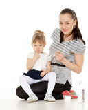 Young mother feeds  her baby. Young mother feeds  her baby on a white background. Happy family Royalty Free Stock Photo