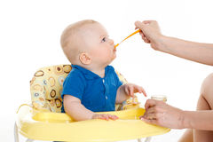 Young mother feeds  her baby. Royalty Free Stock Images