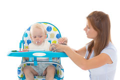 Young mother feeds  her baby. Young mother feeds  her baby on a white background. Happy family Royalty Free Stock Photos
