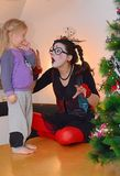 Girl-mime entertains little baby girl. A young mother, in the form of a mime, is fascinatingly telling something to her little daughter near the Christmas tree stock photo