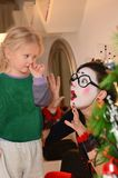 Girl-mime entertains little baby girl. A young mother, in the form of a mime, is fascinatingly telling something to her little daughter near the Christmas tree stock photos