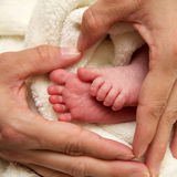 Young mother formed a heart with her hands and is holding her baby girls feet. In front of white blanket Stock Photography